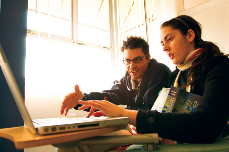 Male and female student studying together on laptop