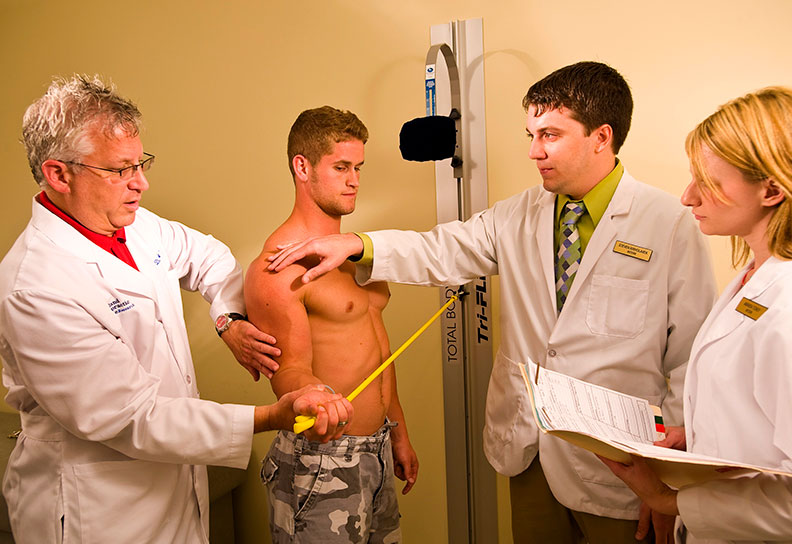 Chiropractic students interning in the health center, learning how to assess a patient